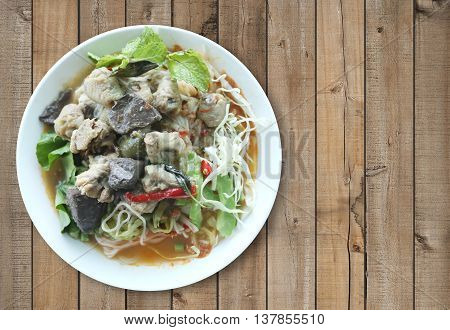 Curry chicken noodles (KHANOM CHIN) with vegetableThis is local Thai foods in Vermicelli rice on wooden background.