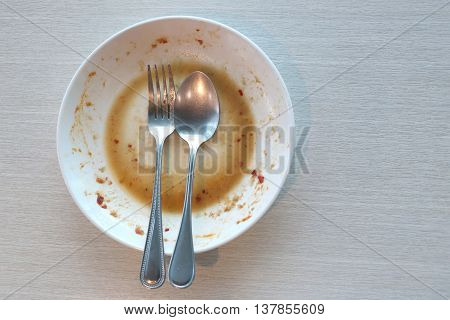 White dish have dirty after put a food and finished eating on table in the restaurant.