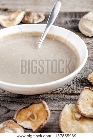 Creamy vegan mushroom soup with champignon and shiitake in white bowl. Wood background. Dry shiitake on front.