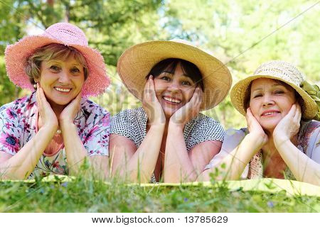 Portrait of three aged women in elegant hats resting on grass