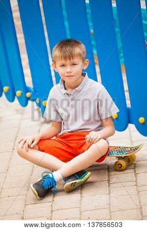 Boy sitting on a skateboard on a blue background