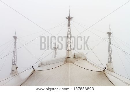 Iron towers and tensioners on the roof of a circus tent in the fog