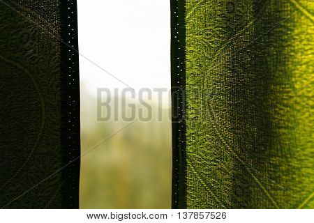 View through window with green curtains background