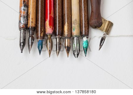 Vintage fountain pen collection. Aged colorful artist pens textured white paper background. Artist tools concept. macro