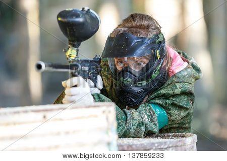 Cool girl shooting from paintball gun. Closeup.