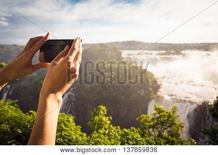 girl taking a photo of Iguassu waterfall with smartphone