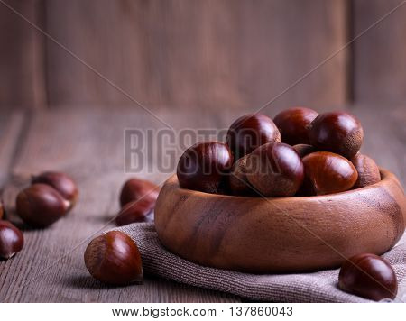 chestnuts in wooden bowl on the old wooden table