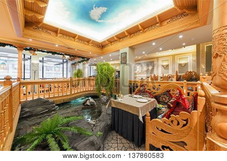 MOSCOW/RUSSIA - DECEMBER 2014. The interior of the deluxe restaurant of Uzbek cuisine - Babay Club in an oriental style. A table near the ornamental pond and a wooden bridge