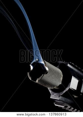 Semi automatic rifle on black with smoke coming from the barrel