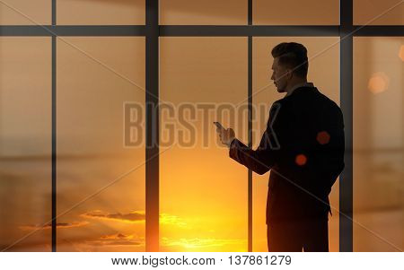 Side view of young businessman using mobile phone against panoramic window with sunset view