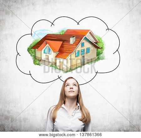 Attractive european businesswoman daydreaming about real estate on concrete background. Mortgage concept