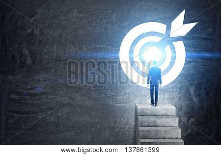 Targeting concept with businessman on top of concrete ladder leading to abstract illuminated dartboard sketch on chalkboard background