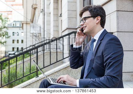 Side view of handsome young businessman sitting outside on building stairs using laptop and having mobile phone conversation