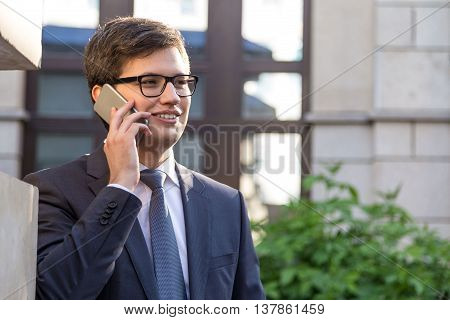Portrait of attractive smiling businessman standing outside and having mobile phone conversation