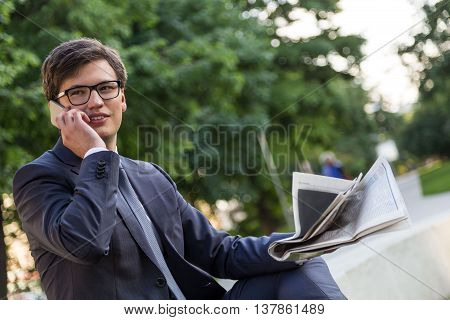 Side view of thoughtful handsome businessman in suit sitting outside holding newspaper and talking on cellphone. Blurry green trees in the background