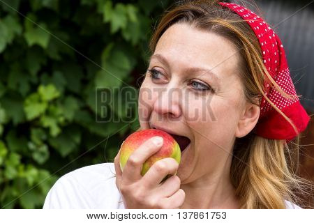 A young market woman biting with relish in a fresh apple