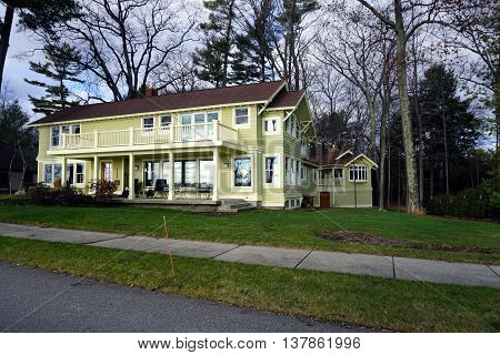 HARBOR SPRINGS, MICHIGAN / UNITED STATES - DECEMBER 25, 2015: A large yellow home with a balcony on East Bluff Drive in Harbor Springs, Michigan, with a view of Little Traverse Bay.