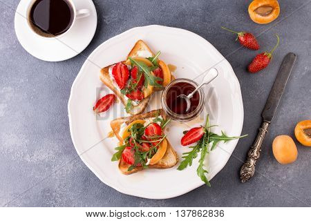 French toast with fresh strawberries, peaches and arugula, poured with maple syrup