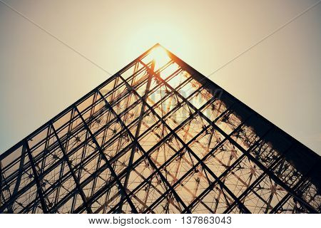 PARIS, FRANCE - MAY 13: Louvre museum pyramid with sun on May 13, 2015 in Paris. With over 60k sqM of exhibition space, Louvre is the biggest Museum in Paris.