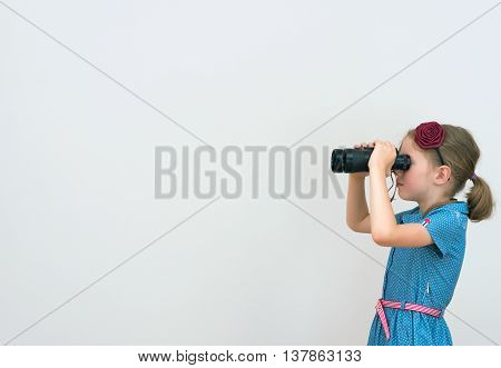 Little Girl Looking Through Binoculars. Space For Your Text.