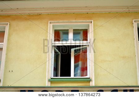 small old open window with yellow facade