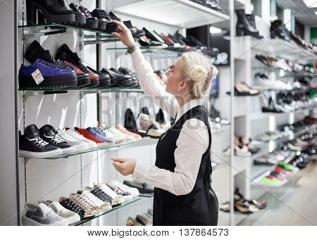 Blonde woman purchasing footwear in the mall