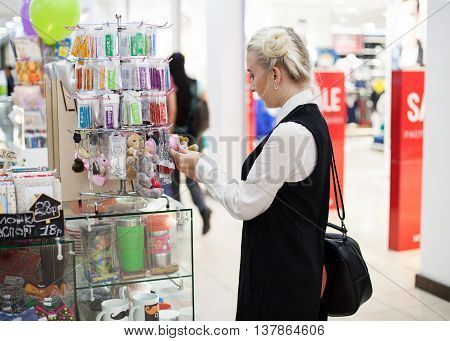 Woman doing shopping in the mall choosing trinket toys at the showstand