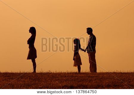 Silhouette of a angry wife  turning back while her husband and daughter are looking at her.