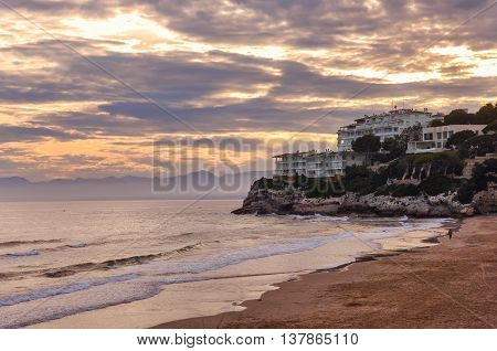 Deserted beach at sunset beautiful cloudscape resort on rock man running along the shore. Salou Spain. Summer vacations concept. Horizontal.