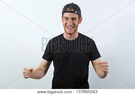 Joyful, Very Happy Smiling Young Adult Male in Dark T-Shirt and Baseball Hat Worn Backwards