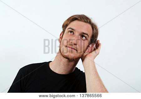 A Young Adult Male with His Hand Near His Ear. Gesture Can Not Hear Without Listening, Talking Louder. Wearing Dark T-Shirt