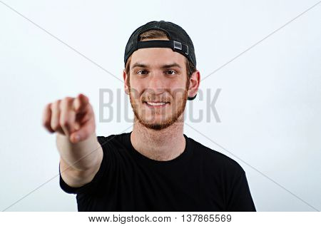 Smiling Young Adult Male in Dark T-Shirt and Baseball Hat Worn Backwards Pointing Towards the Viewer