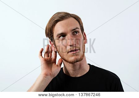 A Young Adult Male Wearing Dark T-Shirt with His Hand Near His Ear. Gestures Can Not Hear or Talk Louder.
