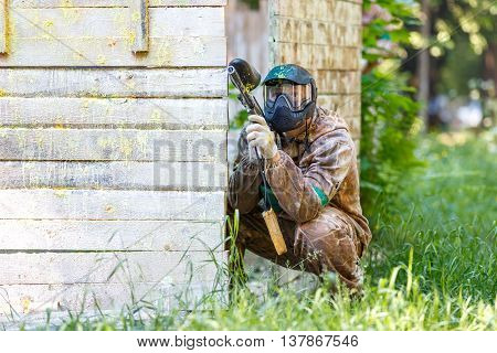 Young man holding paintball marker with yellow paint splashes