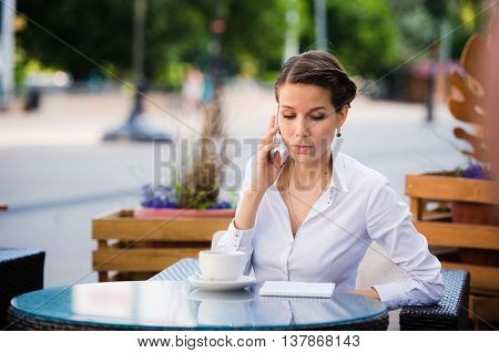 Good business talk. Cheerful young businesswoman talking on the mobile phone and holding cup of coffee while standing outdoors.