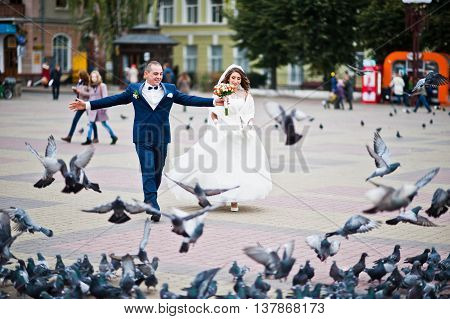 Wedding Couple Walk To The Central Square Dispersing Flock Of Pigeons