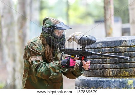 Cool girl with paint gun playing paintball game