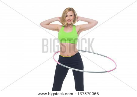 Beautiful middle aged blond fit woman in green bra top and black pants doing sport exercise with hula hoop. Isolated over white background. Copy space.