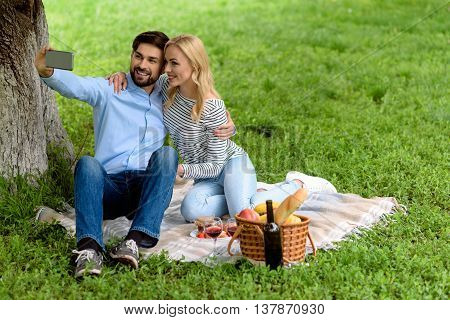 Relaxed man and woman are making selfie in nature. They are sitting on blanket on grass and embracing. Man is holding mobile phone. Woman is smiling happily