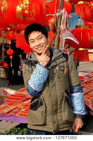 Jun Le China - January 25 2014: Friendly teenage youth selling Chinese Lunar New Year decorations at the family's roadside booth