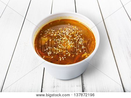 Asian japanese cuisine - red fish soup with sesame closeup at white wood background, diet and vegetarian food