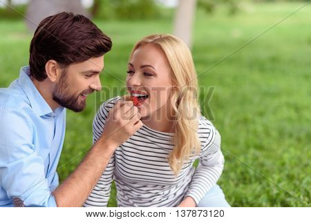 Joyful young loving couple has romantic picnic. Woman is eating strawberry from male hand. They are sitting on grass and smiling