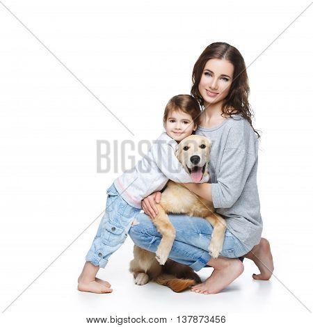 Beautiful young woman with little girl and retriever dog. Mother and daughter isolated over white background. Copy space.