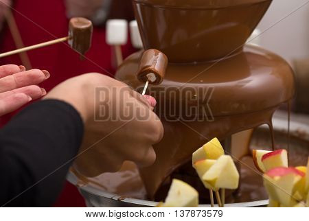 Chocolate fountain and extends a hand to it. Food