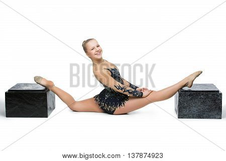 Gymnast girl in beautiful costume sitting in twine between two boxes. Isolated over white background. Copy space.