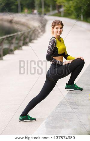 Sporty girl streching her leg in park on summer day