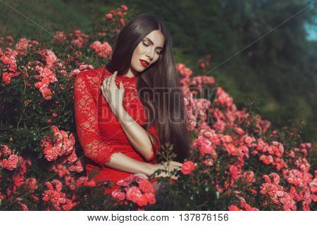 Woman with long hair sitting in the bushes of roses.