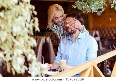 Guess who it is. Carefree young woman is covering male eyes secretly. She is standing and smiling. Man is sitting at table in restaurant