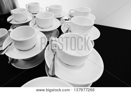 White tea cups with saucers and teaspoons compiled stack.