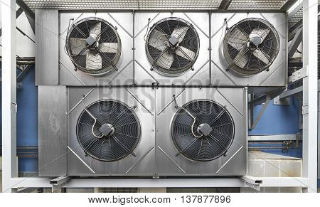 Industrial air conditioning units. Five cooling modules hang on the wall of a building.